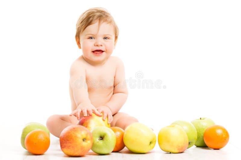 Tragen Sie für Baby, glückliches Kindermädchen mit den Äpfeln Früchte, die über Weiß sitzen lizenzfreies stockfoto