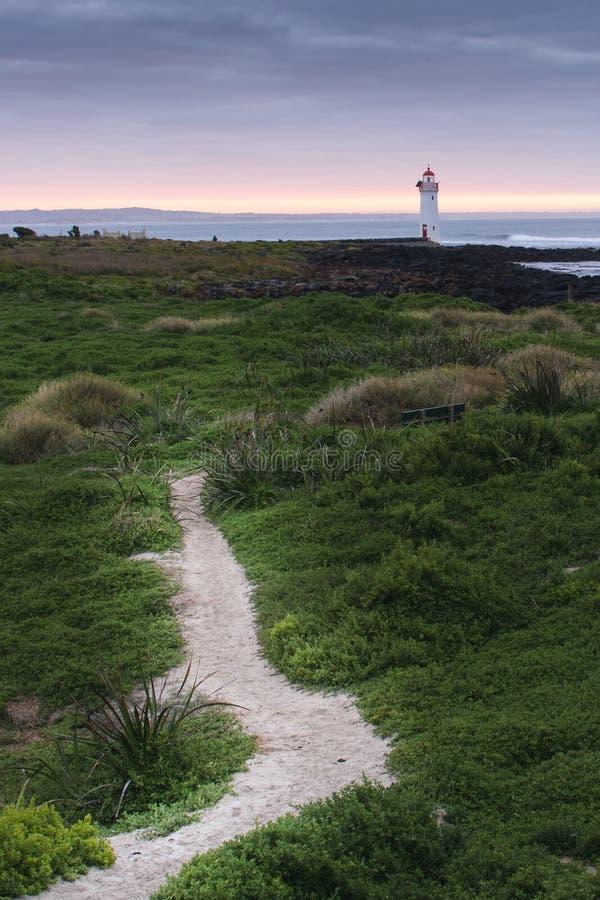 Tragen Sie feenhaften Leuchtturm bei Sonnenaufgang mit den Felsen und Weg, die in Richtung zu führen lizenzfreie stockfotos