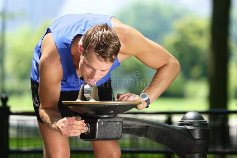 Tragen Sie Trinkwasser des Mannes vom Brunnen des allgemeinen Parks zur Schau lizenzfreies stockfoto