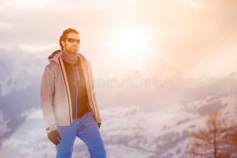 Tragende Anorakjacke des Skifahrermannsonderkommandos mit Sonnenbrilleporträt erforschendes schneebedecktes Land, das mit alpinem lizenzfreie stockfotografie