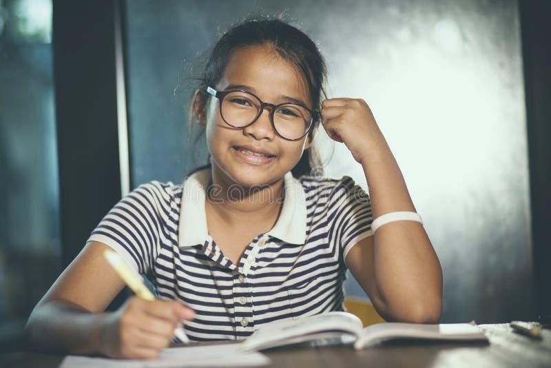 Tragende Augengläser des asiatischen Jugendlichen, die Hausaufgaben mit Stapel von erledigen lizenzfreie stockbilder