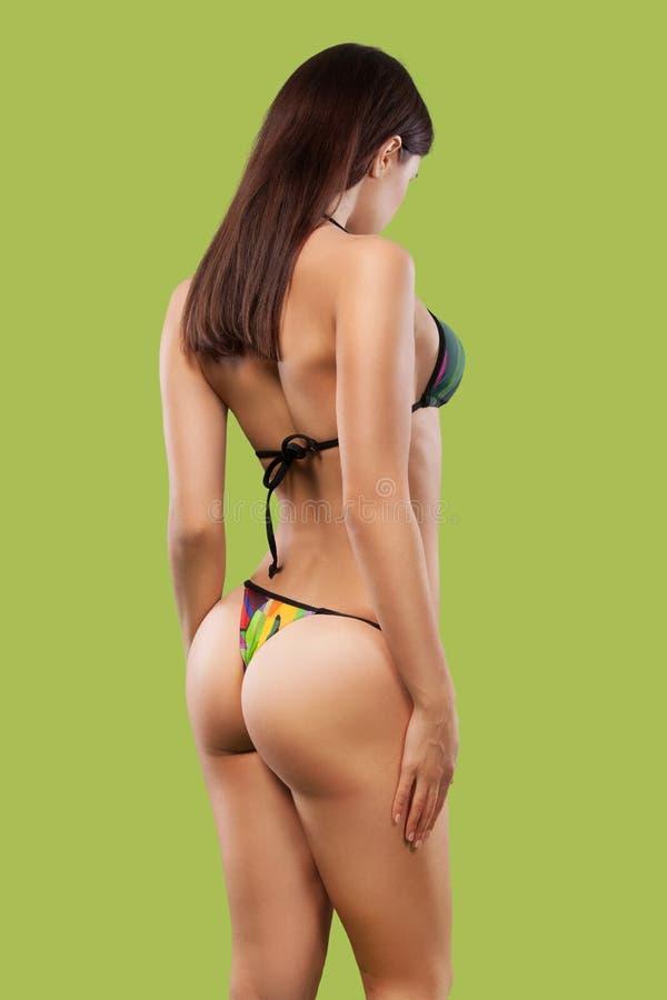 Tragende Badebekleidung der sexy Blondine, die auf Farbhintergrund aufwirft Vollkommene Karosserie Bikinikatalog lizenzfreie stockbilder