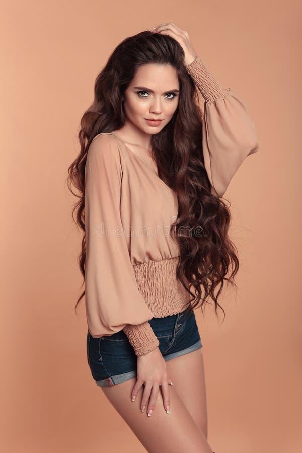 Tragende Bluse des modernen schönen Mädchens mit langen Ärmeln und lizenzfreie stockfotos