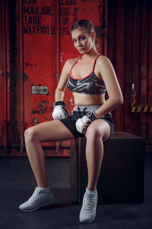 Tragende Boxhandschuhe der Frau, die nahe Ring sitzen lizenzfreies stockbild