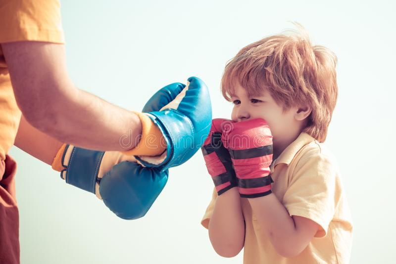 Tragende Boxhandschuhe des älteren Trainers und des kleinen Jungen Porträt eines entschlossenen älteren Boxers mit wenigem Jungen lizenzfreies stockfoto