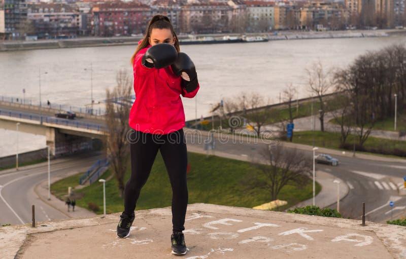 Tragende Boxhandschuhe des jungen Mädchens, die einen Durchschlag - Kampfkünste werfen stockbild