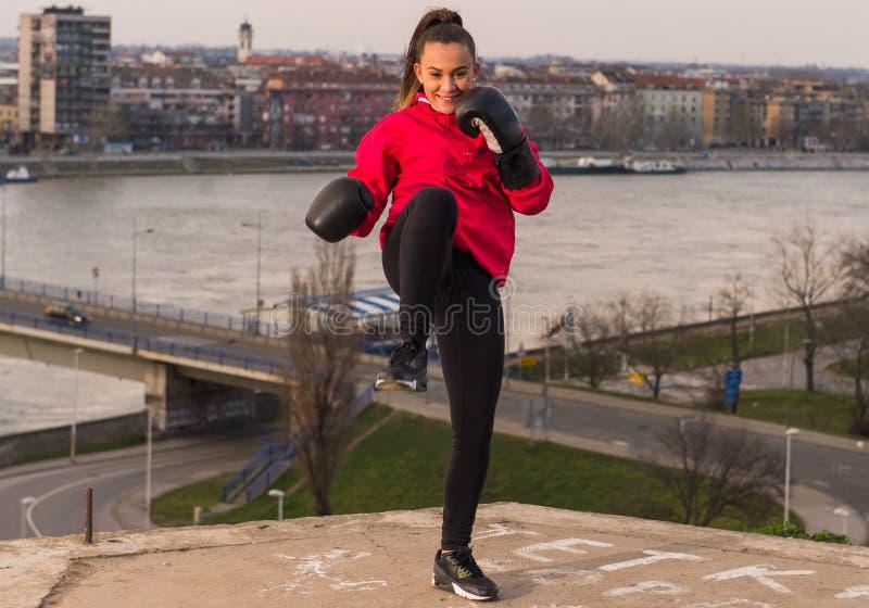 Tragende Boxhandschuhe des jungen Mädchens, die einen Durchschlag - Kampfkünste werfen lizenzfreies stockbild
