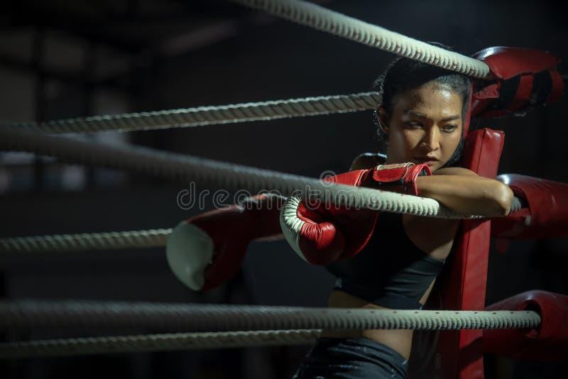 Tragende Boxhandschuhe des umgekippten jungen K?mpferboxer-M?dchens in der Turnhalle stockfotografie