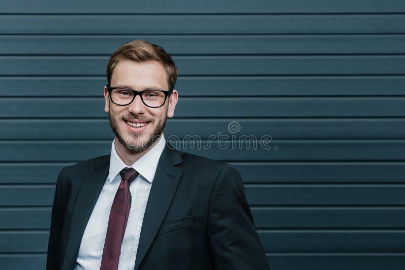 Tragende Brillen des hübschen stilvollen jungen Geschäftsmannes und Lächeln an der Kamera stockfotos