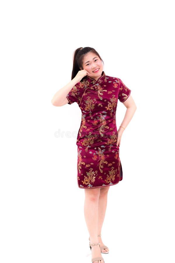 Tragende Chinesen der jungen asiatischen Frau kleiden traditionelles cheongsam mit dem Klemmen ihrer Backen und täuschen Lächeln  stockbild