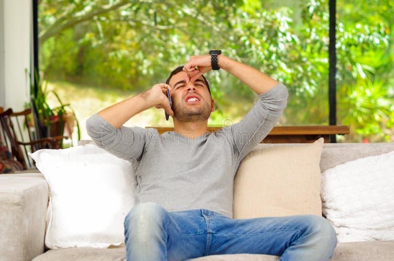 Tragende Denimjeans des hispanischen Mannes mit grauer Strickjacke stockbild