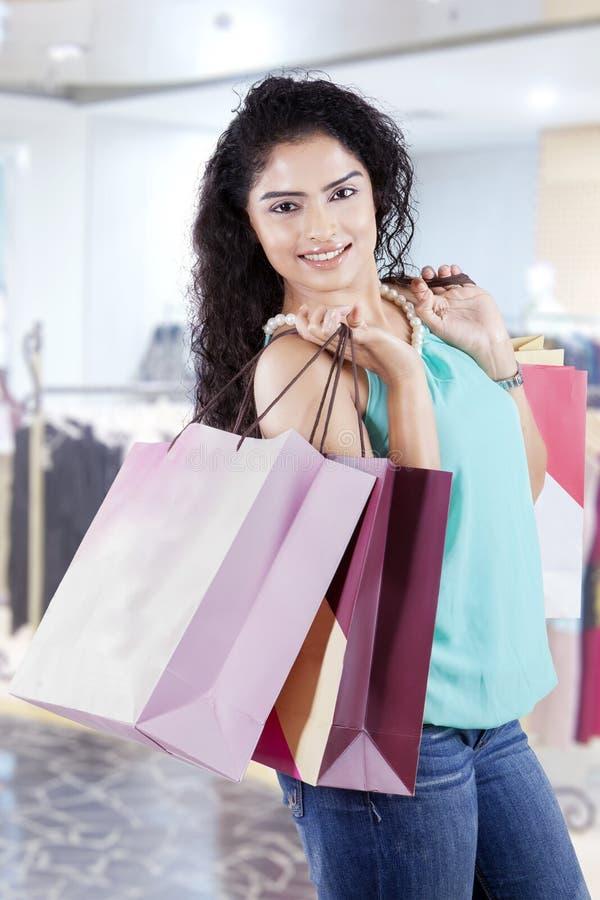 Tragende Einkaufstaschen der glücklichen indischen Frau stockfotografie