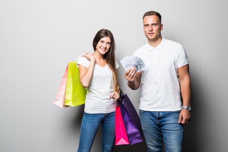 Tragende Einkaufstaschen der glücklichen jungen Paare, die Geldbanknoten zeigend, die über weißem Hintergrund lokalisiert stehen stockfoto
