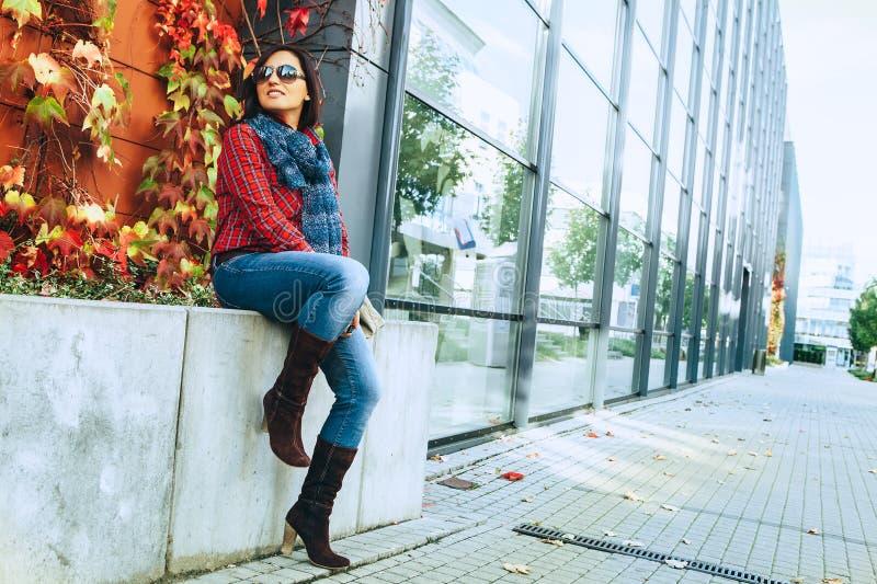 Tragende Frau der Mode sitzt nahe modernem Einkaufszentrum lizenzfreies stockfoto