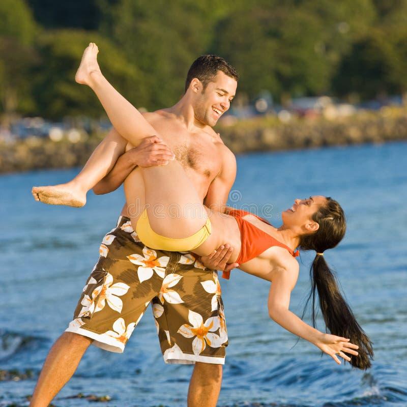 Tragende Freundin des Freundes am Strand lizenzfreies stockfoto