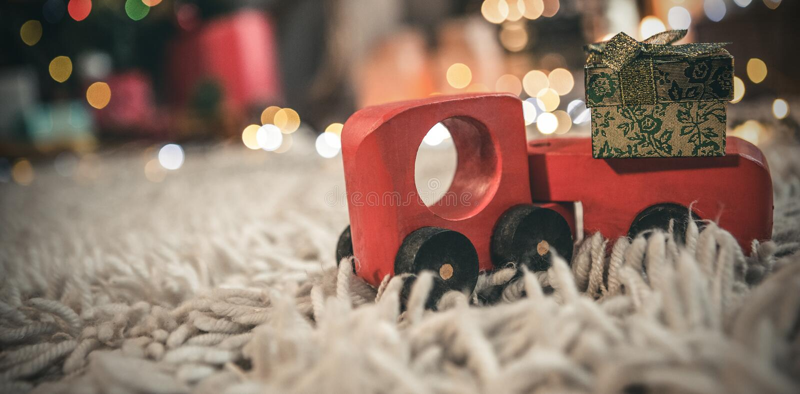 Tragende Geschenkbox des Spielzeugautos Weihnachts lizenzfreie stockbilder