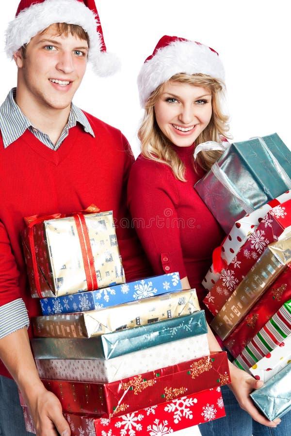 Tragende Geschenke der Weihnachtseinkaufen-Paare stockfotos