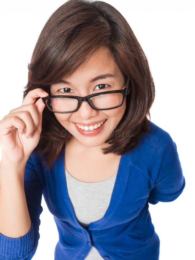 Tragende Gläser der Frau, die oben glückliches Lächeln schauen lizenzfreie stockbilder
