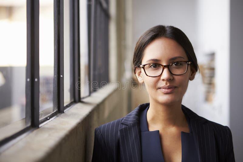 Tragende Gläser der jungen Mischrassegeschäftsfrau, Porträt stockbild