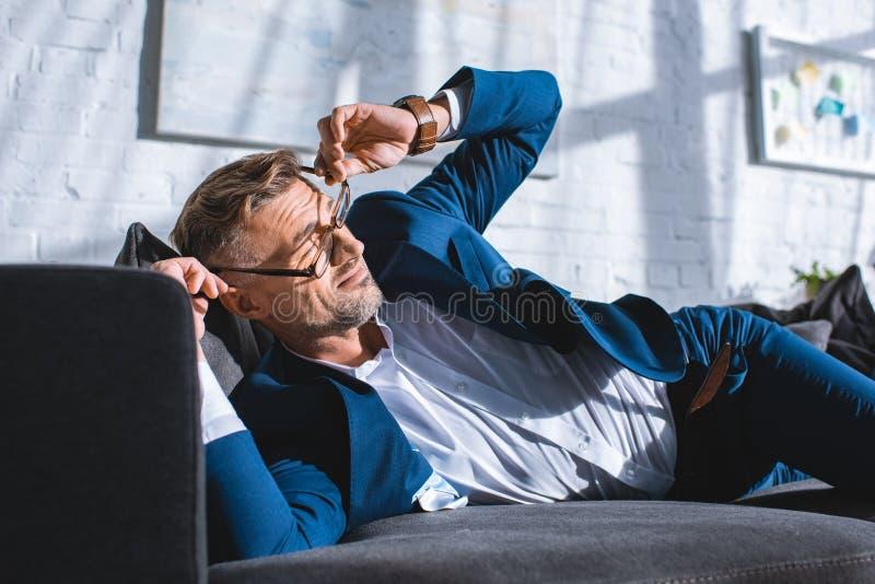 tragende Gläser des betrunkenen Geschäftsmannes beim Lügen lizenzfreies stockfoto