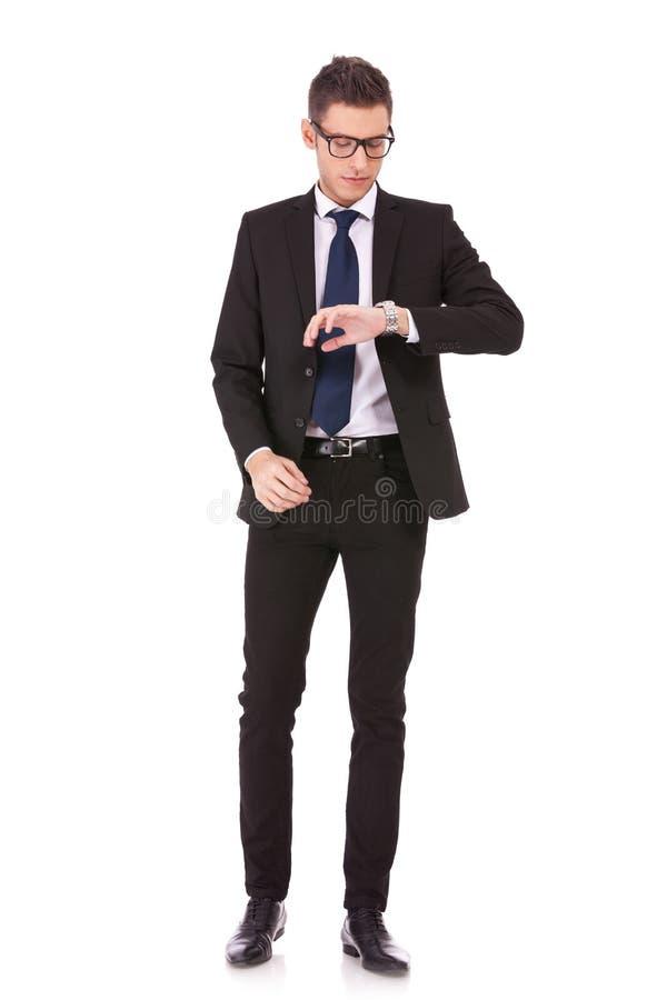 Tragende Gläser des Geschäftsmannes, die Uhr betrachten lizenzfreies stockfoto