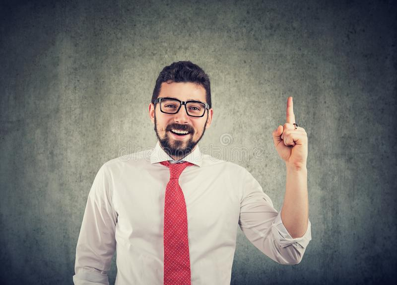 Tragende Gläser des Geschäftsmannes mit einer guten Idee, die mit seinem Finger oben und dem Lächeln zeigt lizenzfreies stockbild