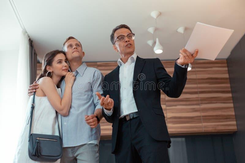 Tragende Gläser des Grundstücksmaklers, die mit den Kunden sagen über das Haus sprechen stockfoto
