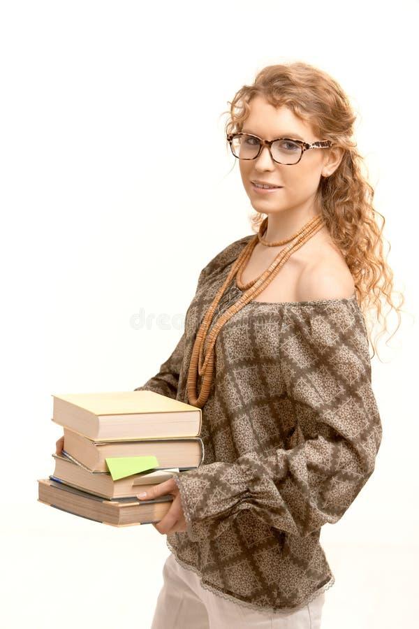 Tragende Gläser des hübschen Mädchens mit Büchern stockfotografie