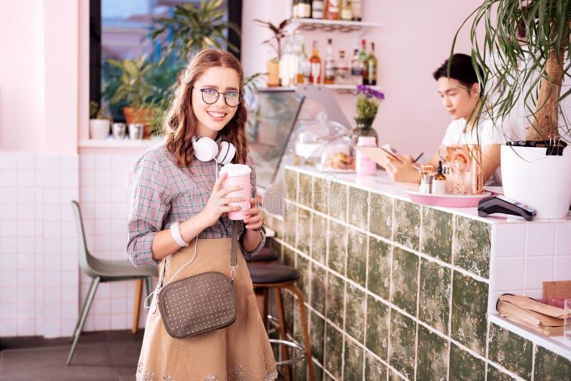 Tragende Gläser des modernen modernen Studenten, die in der Kaffeestube stehen stockbild