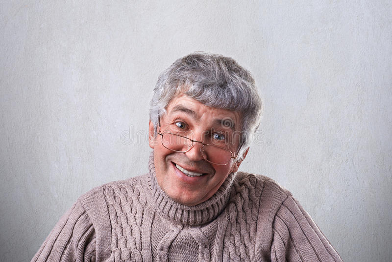 Tragende Gläser eines positiven netten netten reifen Mannes, die nett die Kamera hat leichtes Lächeln untersuchen Lächelnder älte stockfoto