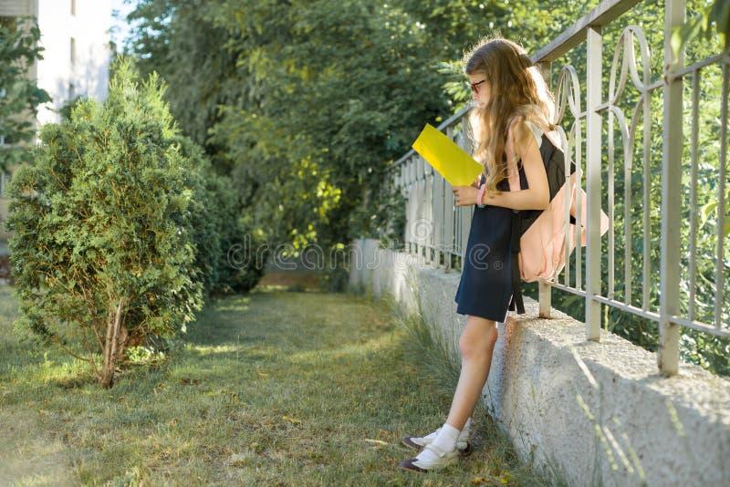 Tragende Gl?ser des Schulm?dchengrundsch?lers mit dem Rucksackleseschulnotizbuch, stehend nahe Zaun, im Schulhof lizenzfreie stockfotografie