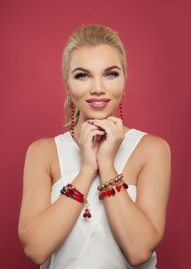 Tragende goldene Ohrringe und Armband der Mode der hübschen Frau mit roten Edelsteinsteinen lizenzfreies stockfoto