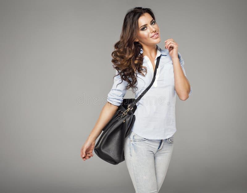 Tragende Handtasche der Brunette Frau lizenzfreie stockfotos