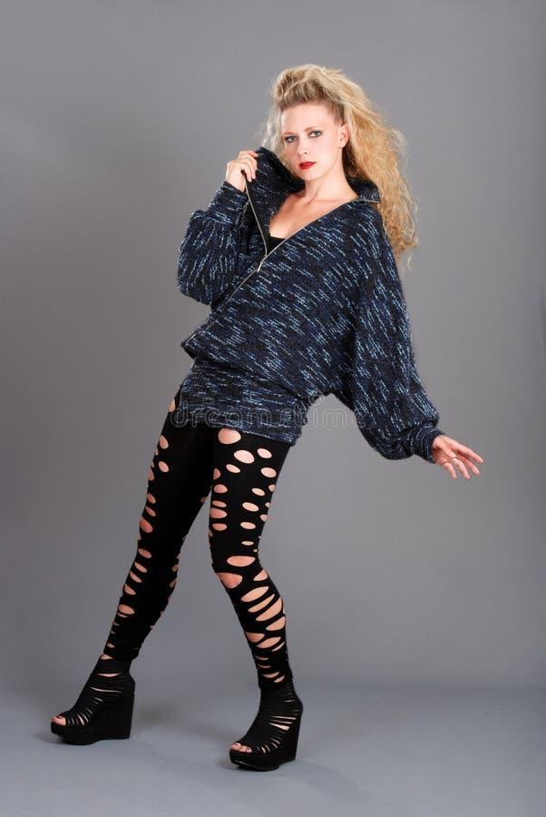 Tragende Hosen der Frau mit Löchern und Strickjacke stockfoto