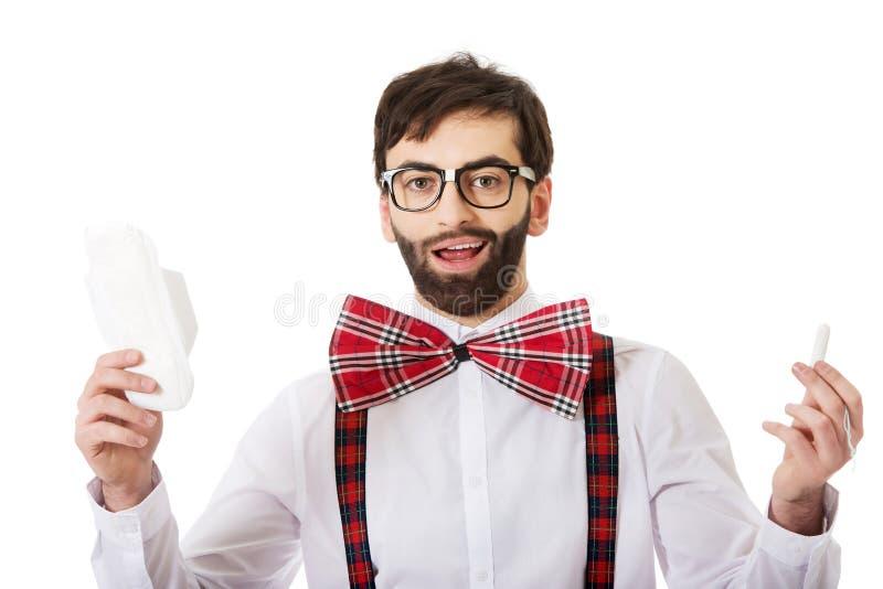 Tragende Hosenträger des Mannes, die Menstruationsauflage halten stockfoto