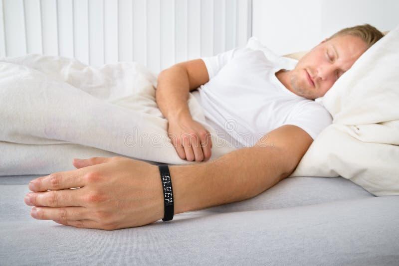Tragende intelligente Manschette Schlafens des jungen Mannes lizenzfreies stockfoto