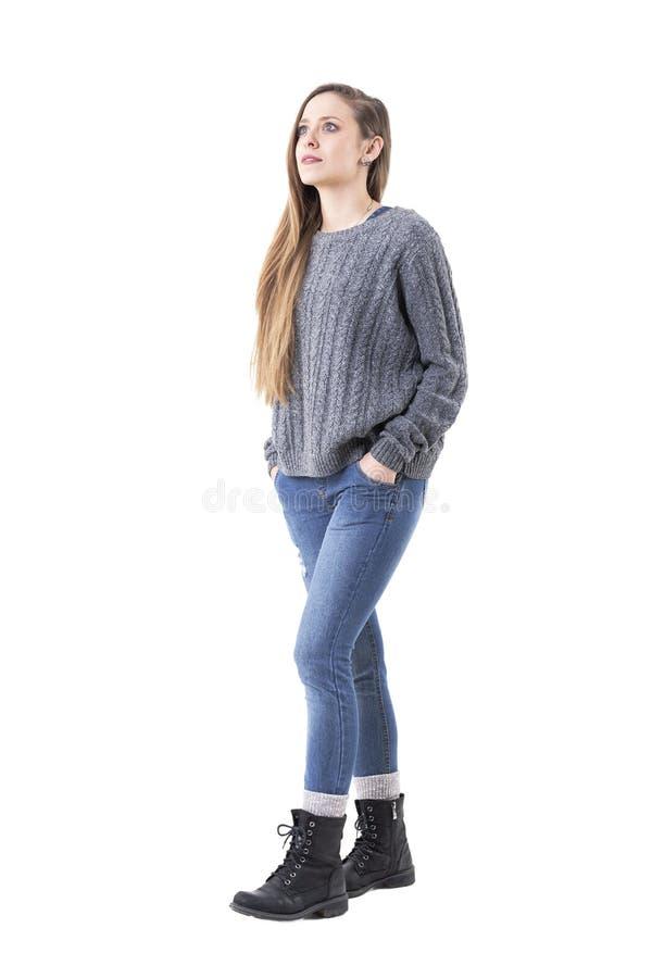 Tragende Jeans der zufälligen jungen netten Frau und graue Strickjacke, die oben überrascht geht und schaut stockbild