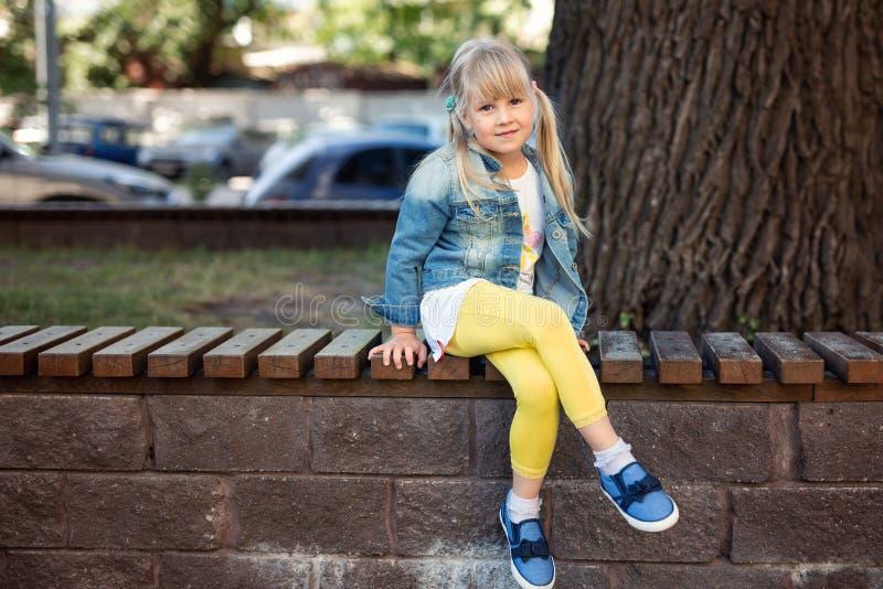 Tragende Jeans des entzückenden blonden kaukasischen Vorschüler Fashionista-Mädchens und helle gelbe Leggins, die über Holzbank s stockbilder