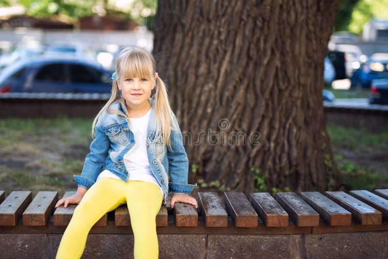 Tragende Jeans des entzückenden blonden kaukasischen Vorschüler Fashionista-Mädchens und helle gelbe Leggins, die über Holzbank s stockfotos