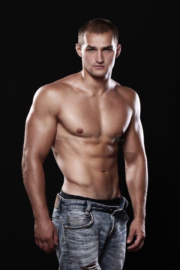 Tragende Jeans des jungen und reizvollen Kerls stockbilder