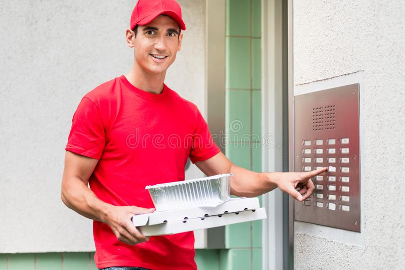 Tragende Kästen des Pizzaboten unter Verwendung der Wechselsprechanlage lizenzfreie stockfotografie
