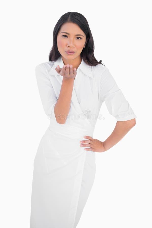 Tragende küssende Kamera des eleganten dunkelhaarigen Modells weißes Kleider stockfoto