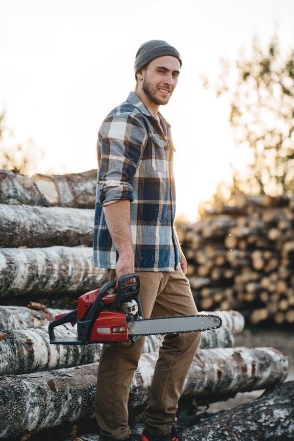 Tragende Kettensäge des Griffs des karierten Hemds des bärtigen starken Holzfällers in der Hand für Arbeit über Sägemühle stockfoto