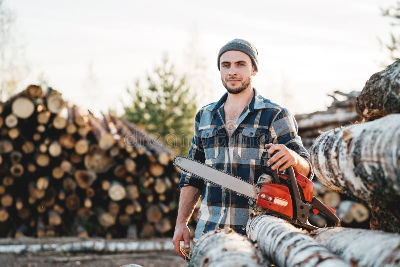 Tragende Kettensäge des Griffs des karierten Hemds des starken Holzfällers in der Hand für Arbeit über Sägemühle stockfoto