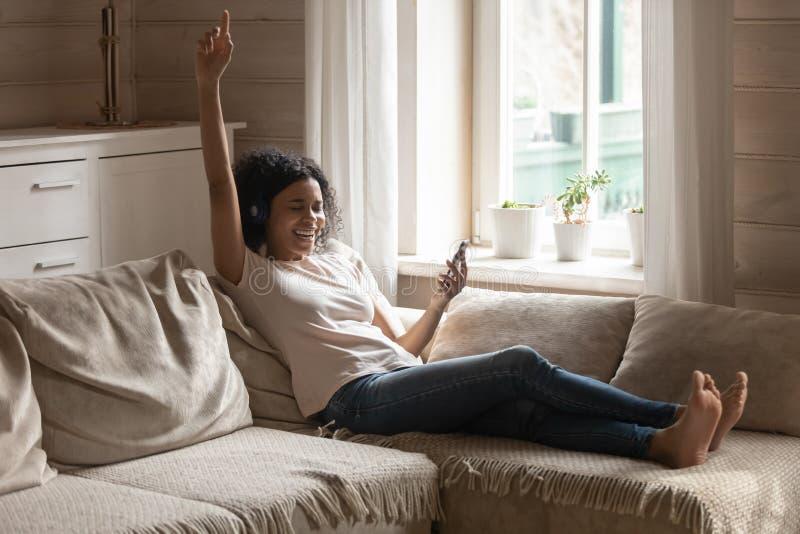 Tragende Kopfhörer der Afrikanerin, die auf der Couch singt Lieblingslied stillstehen lizenzfreie stockfotografie