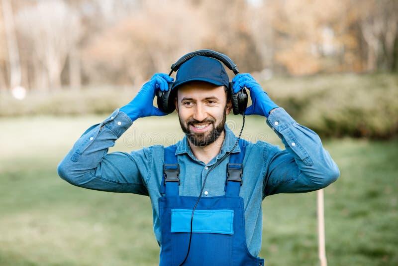 Tragende Kopfhörer des Gärtners draußen lizenzfreie stockbilder