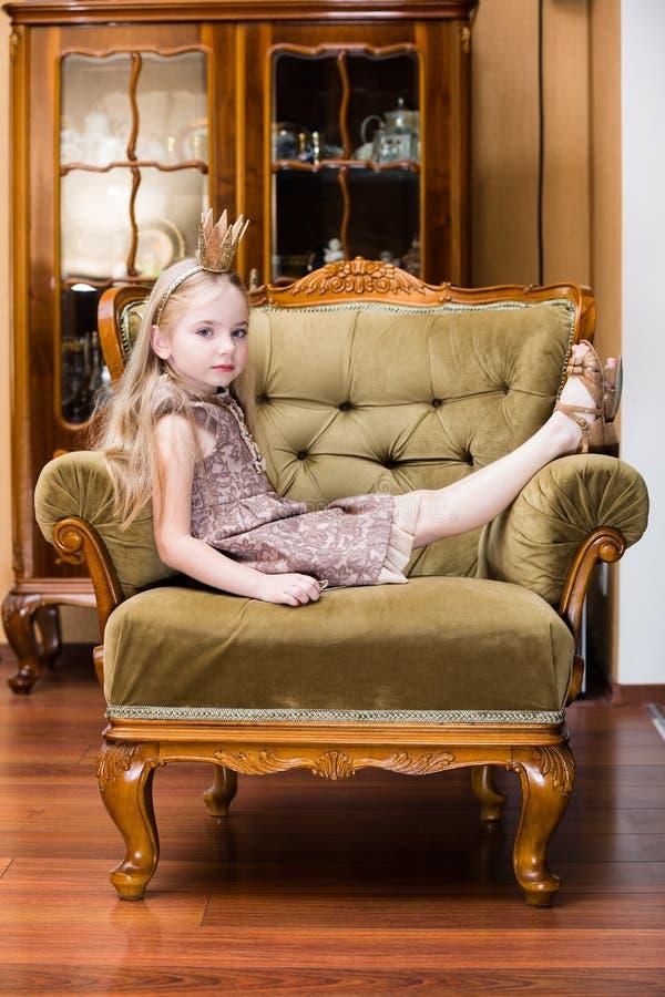 Tragende Krone des blonden Haares des kleinen Mädchens, die am Stuhl steht stockfotos