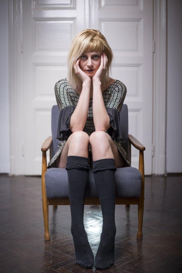 Tragende legere Kleidung der schönen jungen Blondine, die im Stuhl stationiert stockfotos