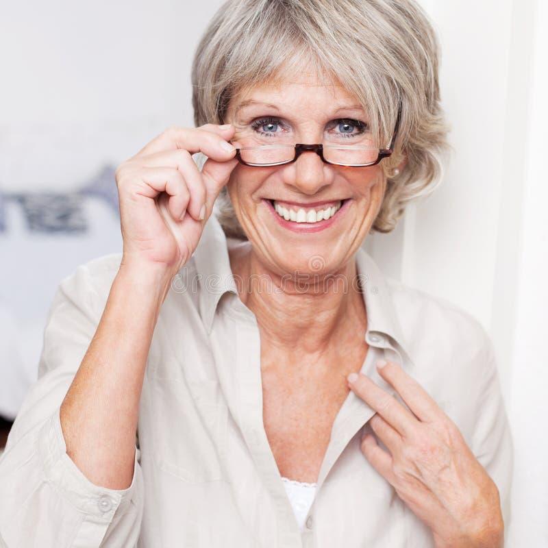 Tragende Lesebrille glücklicher älterer Dame lizenzfreie stockbilder