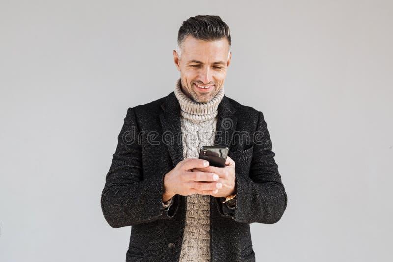 Tragende Mantelstellung des attraktiven Mannes stockfoto